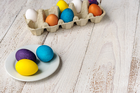 colorant: Colored easter eggs in carton and plate on wooden white shabby background