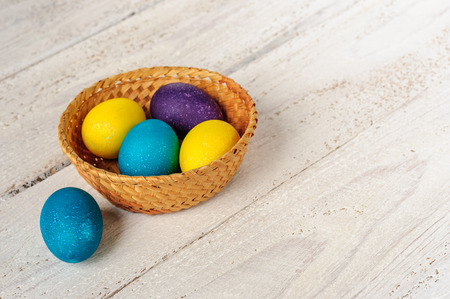 colorant: Colored easter eggs in straw basket on wooden white shabby background