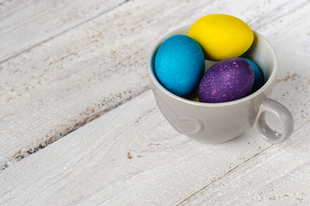 colorant: Colored easter eggs in grey ceramic cup on wooden white shabby background
