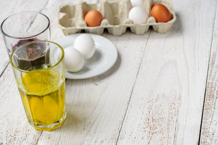 colorant: On wooden white shabby background are eggs in carton, eggs on plate and two glasses of food dye with eggs