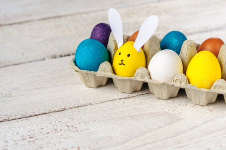 colorant: Colored easter eggs in carton with egg-shaped bunny on wooden white shabby background