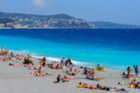 cote d'azure: View of the beach in Nice, France, near the Promenade des Anglais. tourists, sunbeds on summer hot day, blurred