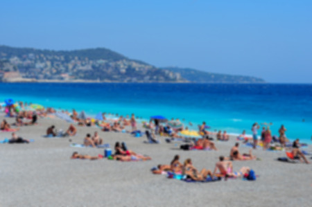 cote d'azure: View of the beach in Nice, France, near the Promenade des Anglais. tourists, sunbeds and umbrellas on summer hot day, blurred