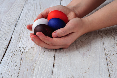 colorant: Colored easter eggs in hands on wooden white shabby background