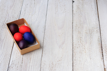 colorant: Colored easter eggs in carton on wooden white shabby background Stock Photo