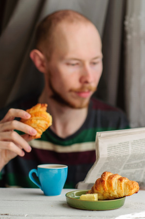 Blurred young man eats his breakfast, coffee, croissant and reads newspaper photo