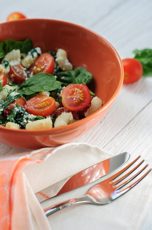 maccheroni: Salad with pasta, spinach, tomatoes cherry and ricotta on white shabby wooden background