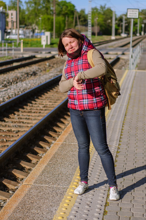 waits: Girl with backpack waits train on train station