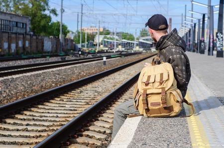 waits: Young man waits train on railway platform Stock Photo