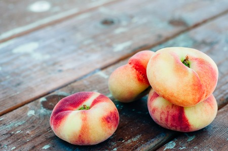 saturn: Fresh Saturn peaches on old wooden background Stock Photo