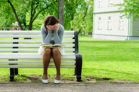 person reading: Young woman reads a book with emotions on a bench in park Stock Photo