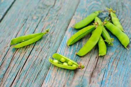 peas in a pod: Ripe fresh green peas in pod on shabby wooden background Stock Photo