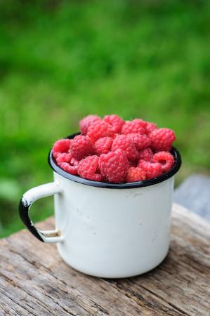 enamel: White enamel can and mug with fresh raspberry