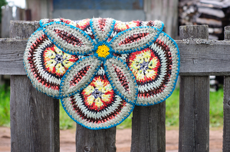 Russian vintage knitted round rug hanging on a old wooden fence