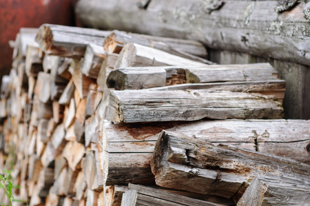 stack of firewood: Stack of firewood near old wooden fence