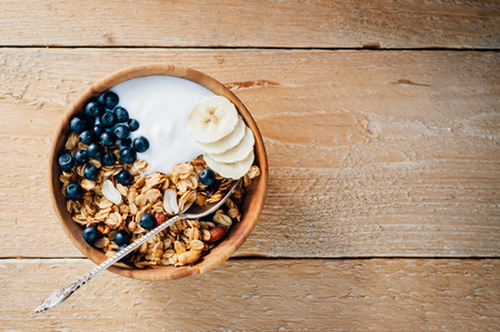 breakfast cup: Homemade oatmeal granola with peanuts, blueberry and banana in wooden bowl, sunny morning