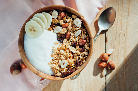 oatmeal bowl: Homemade oatmeal granola with peanuts, blueberry and banana in wooden bowl, sunny morning