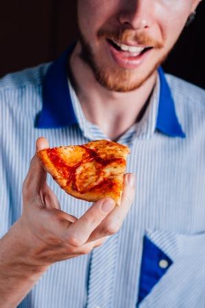 margherita: Young man with beard eating pizza Margherita Stock Photo