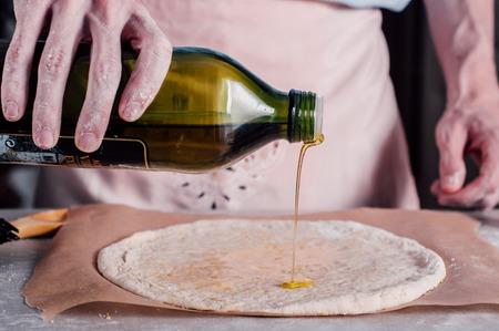 요리 과정에서 피자 반죽을 기름칠하는 남자