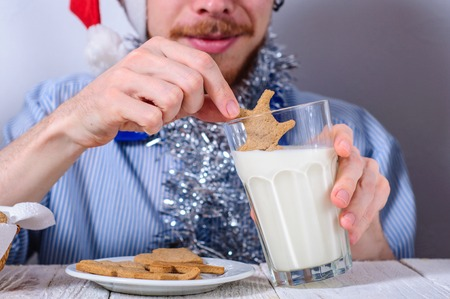 gingerbread man: Young man eating christman gingerbread cookies with glass of milk Stock Photo