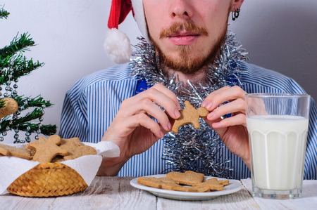 tinted glasses: Young man eating christman gingerbread cookies with glass of milk Stock Photo
