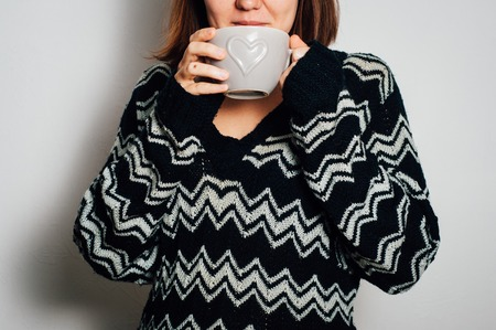 black sweater: Woman in black sweater holding cup with hot drink