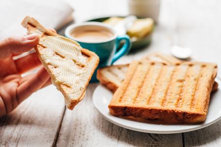 mantequilla: Mano de la mujer que come caf� y tostadas con mantequilla y mermelada para el desayuno