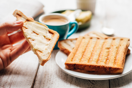 hand jam: Woman hand eating coffee and toast with butter and jam for breakfast