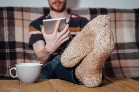 holey: Young man with beard sitting on couch with tablet in holey socks