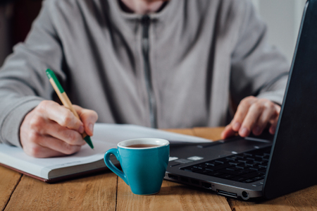 busy beard: Young man with beard writing notes in front of laptop and cup of coffee