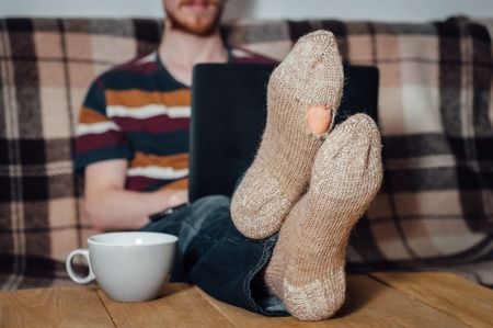 holey: Young man with beard working with laptop in holey socks on table