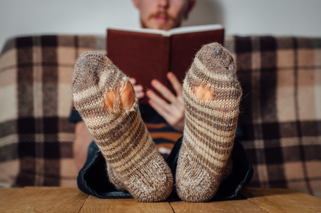 holey: Young man with beard reading book on couch in holey socks