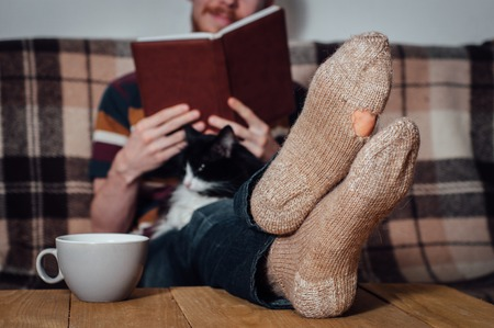 holey: Young man with beard reading book on couch with black white cat in holey socks Stock Photo