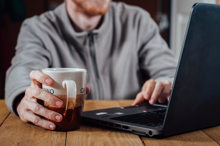busy beard: Young man with beard working with laptop and with cup of coffee