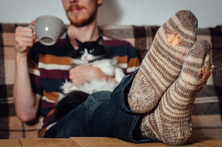 holey: Young man with beard sitting on couch with black white cat in holey socks