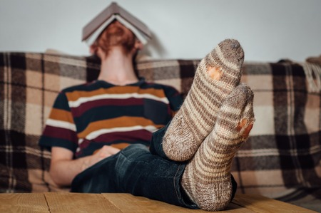 holey: Young man with beard sleeping after book reading on couch in holey socks Stock Photo