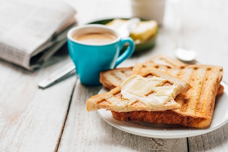 Breakfast with coffee, toasts, butter and jam on white wooden background Stock Photo