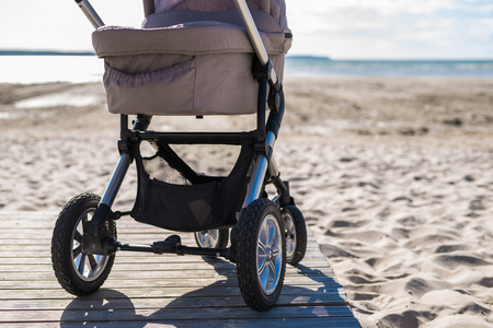 Baby stroller on beach at sunny day