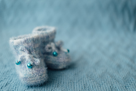 booties: Knitted blue baby boy booties on knitted background