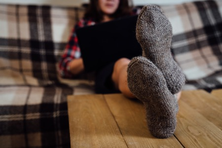 Young woman working with laptop on couch in knitted handmade socks