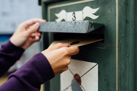 mailing: Mailing letter with wax seal to old postbox on street Stock Photo