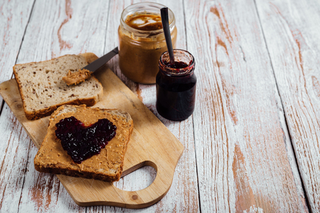 peanut butter and jelly: Homemade peanut butter and heart shaped jelly sandwich on wooden background Stock Photo