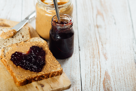Homemade peanut butter and heart shaped jelly sandwich on wooden background 免版税图像