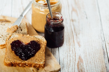 Homemade peanut butter and heart shaped jelly sandwich on wooden background Banco de Imagens