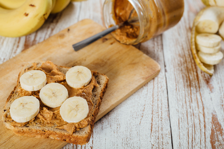 Homemade peanut butter and banana sandwich on wooden background