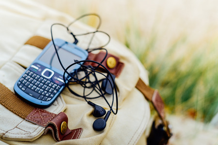 qwerty: Blue old fashioned smart phone with  qwerty keypad and headset on backpack
