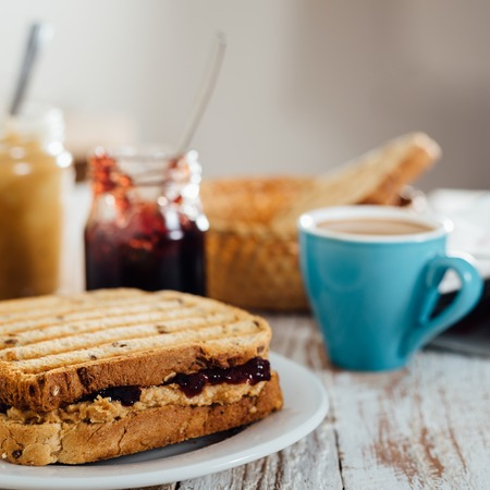 peanut butter and jelly: Breakfast with coffee and homemade peanut butter and cherry jelly sandwich on wooden background Stock Photo