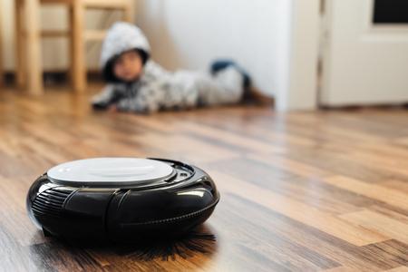 Aspirador robótico en suelo laminado con el bebé en el fondo Foto de archivo - 66718121