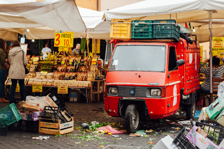 ROME, ITALY - OCTOBER 27, 2015: Little red Piaggio Ape on old italian market on October 27, 2015. With many garbage on the ground