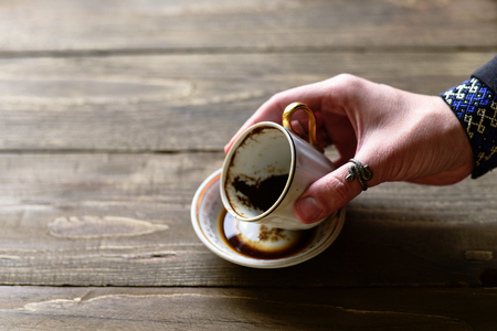 Woman fortuneteller hand with cup of coffee grounds